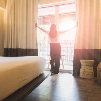 Eine Frau öffnet die Vorhänge in einem Hotel